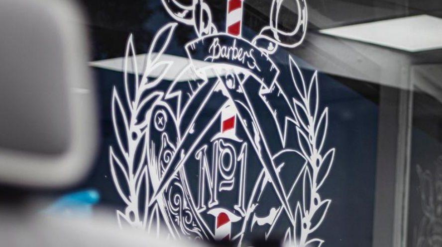 White Barbers No1 logo on a glass screen