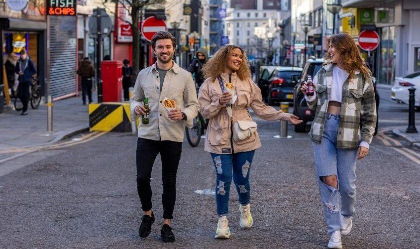 3 friends walking down a street in Liverpool
